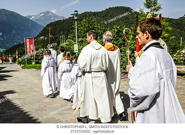 Clergy from the Catholic church including the altar boys walk to the village square on Patronage day in Reith bei Seefeld, Austria