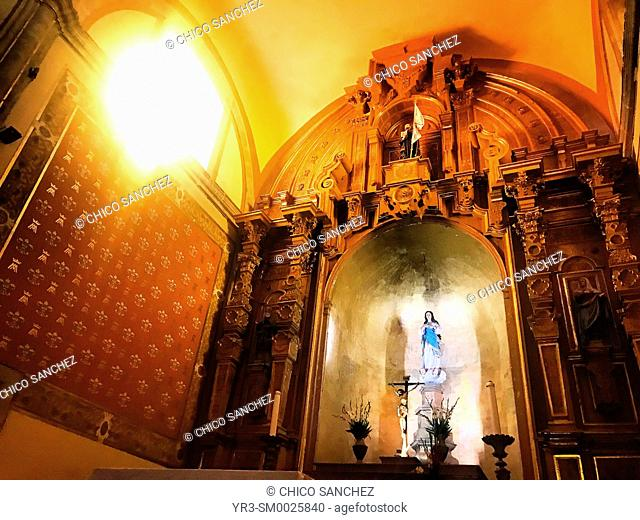 Solar light illuminates and altar of the Virgin Mary and Jesus Christ crucified, decorate a church in the Templo de la Compañia in Oaxaca, Mexico