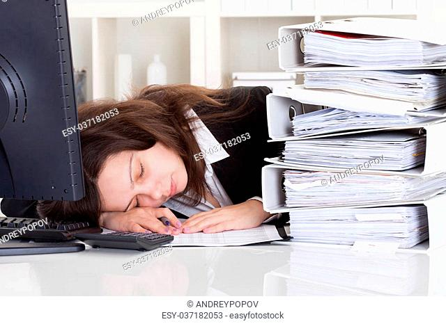 Stressed Businesswoman Sleeping In Office With Stack Of Folders