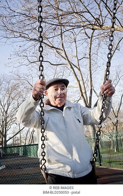 Carefree Hispanic man on swing in park
