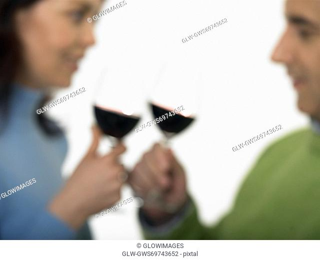 Close-up of a mid adult couple toasting glasses of wine