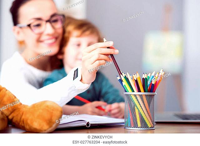 Source of inspiration . Picture of a woman taking a crayon from a pencil cup while sitting at the table with her son