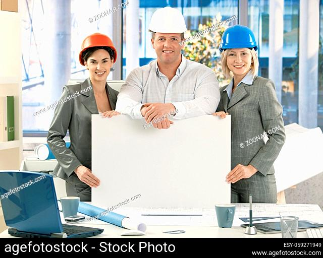 Portrait of confident architect team wearing hardhat, holding blank poster for copyspace