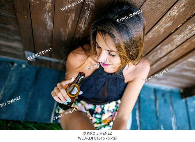 Young woman with beer sitting at wooden hut