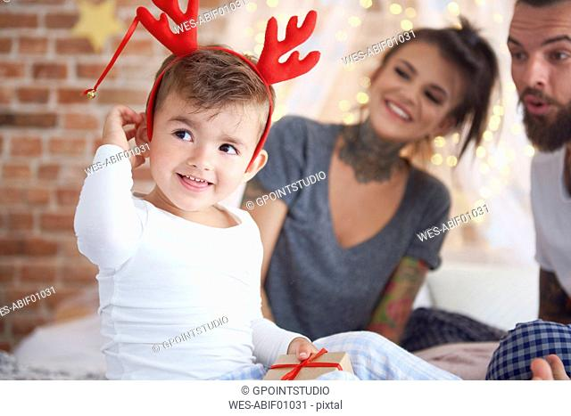 Cute boy in reindeer costume at Christmas time in bed