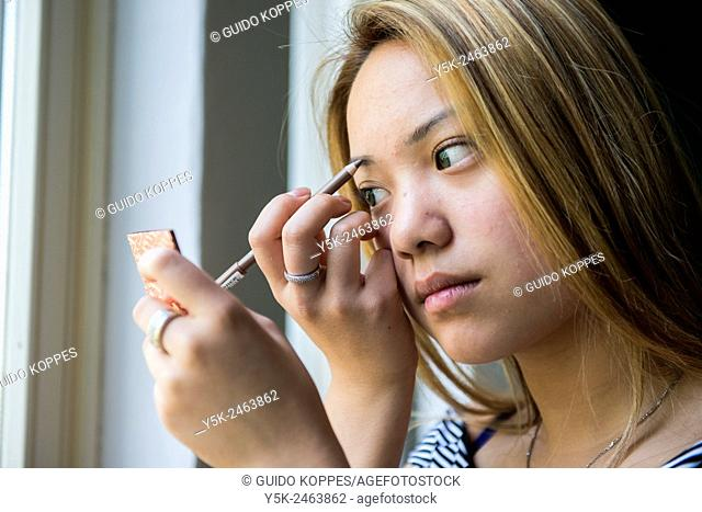 Tilburg, Netherlands. Studio portrait of a young Chinese girl doing her make up