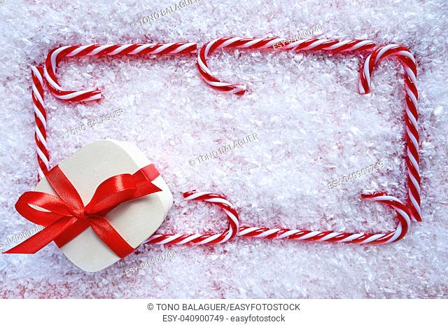 Christmas gift and candy cane frame on snow background