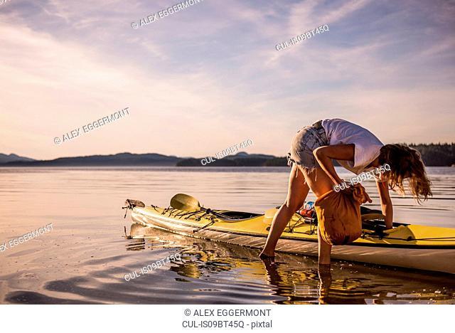 Young female kayaker unpacking kayak, Quadra Island, Campbell River, Canada