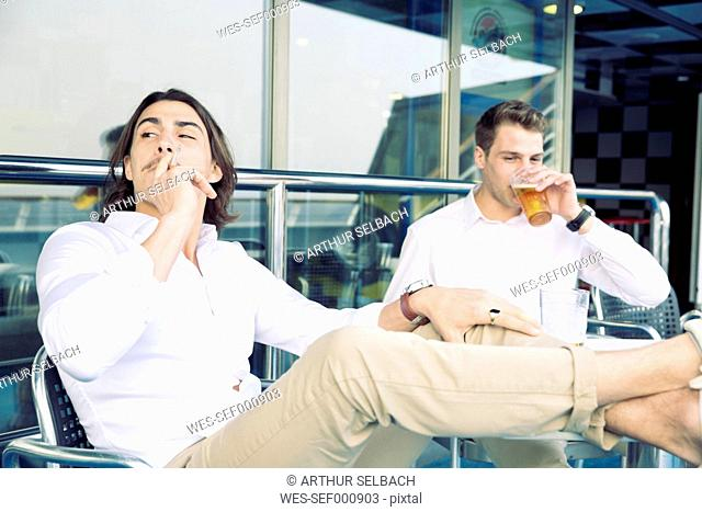 Two young men smoking and drinking beer on cruise ship