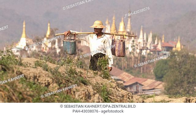 A farmer carries goods in front of the stupas of Shwe Inn Thein Paya near Indaing, Myanmar, 06.04.2013. Photo: Sebastian Kahnert | usage worldwide