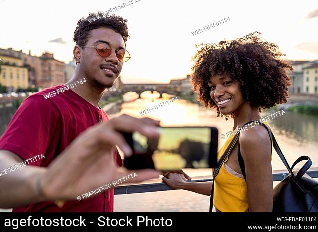 Young tourist couple taking a selfie on a bridge above river Arno at sunset, Florence, Italy