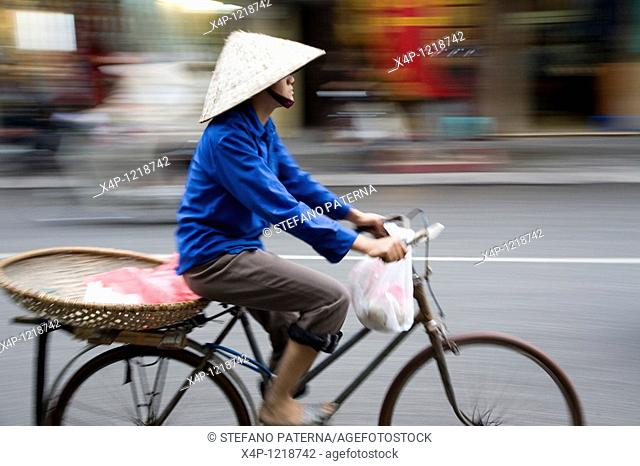 Woman on bicycle in Hanoi, Vietnam