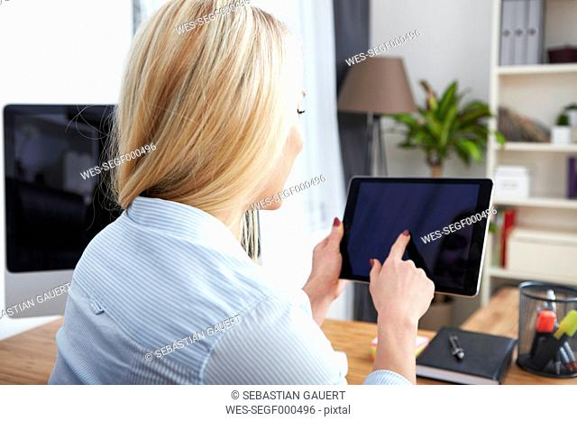 Back view of blond woman sitting at desk using digital tablet