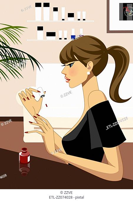 Side view of Young woman applying nail polish
