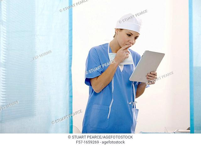 Female Nurse reviewing medical records on a tablet computer