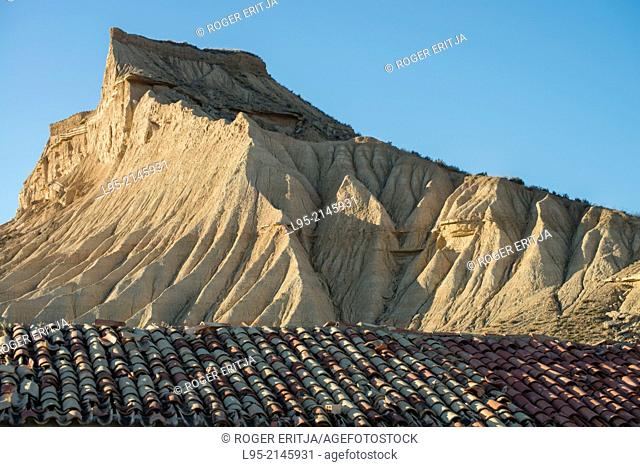 Cliffs eroded by rainfall juxtaposed to ruined traditional cattle shelter on clay-only area of the natural park of Bardenas Reales de Navarra, Navarre, Spain