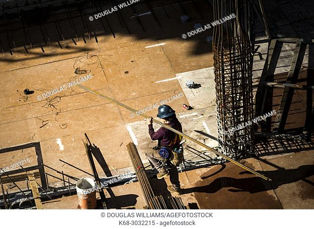 A construction worker carries steel bars at Vancouver House, a tower under construction in Vancouver, BC, Canada