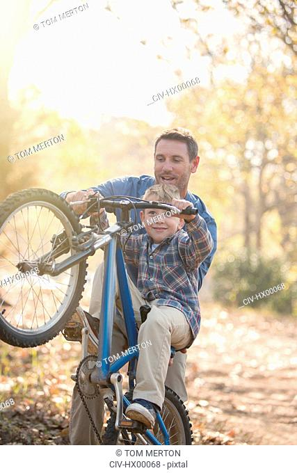 Father teaching son how to do a wheelie in woods