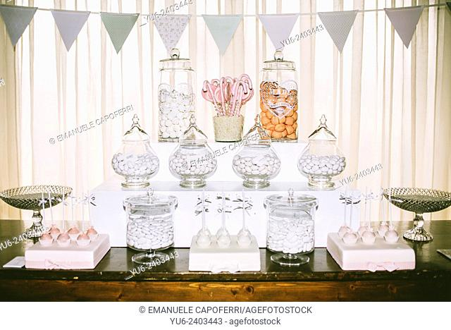 Table with glass jars filled with sweets and confetti