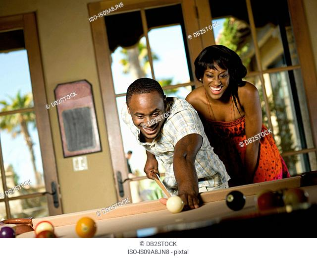 Young couple playing pool together, smiling
