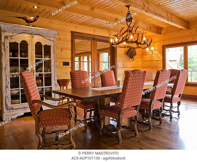 Wooden dining table with red and grey upholstered high-back sitting chairs in dining room on 1st floor inside a cottage style flat log profile and timber home