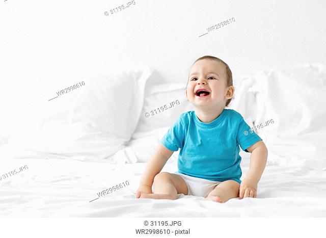 Baby boy with blond hair wearing blue T-shirt sitting on a bed with white duvet