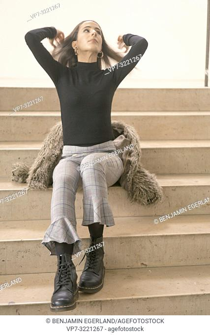 woman sitting on stairs and playing with hairs, in Munich, Germany