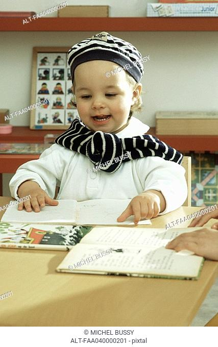 Little girl sitting at table, touching book