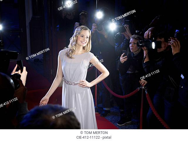 Well dressed female celebrity posing for paparazzi on red carpet
