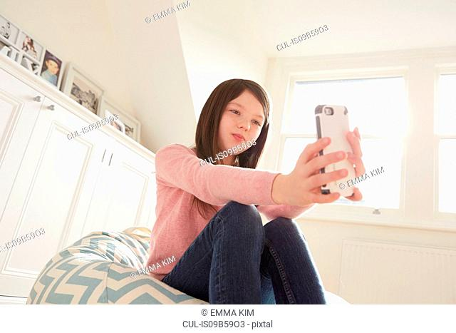 Girl sitting on beanbag chair taking smartphone selfie