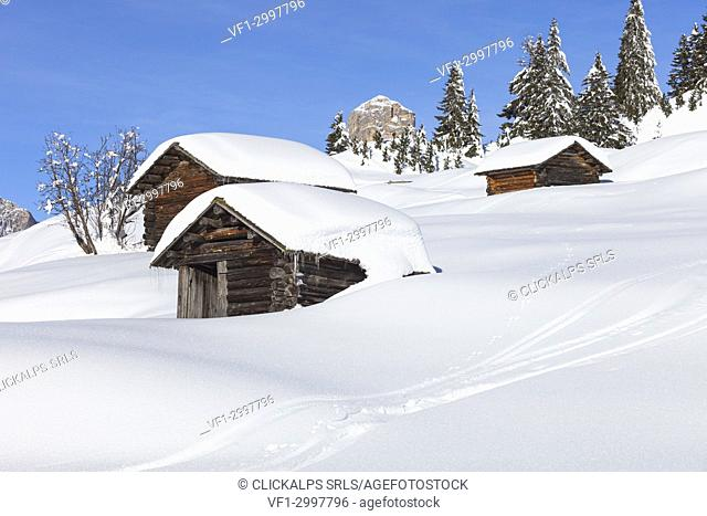 a view of three huts in a winter landscape in Val Badia, Bolzano province, South Tyrol, Trentino Alto Adige, Italy