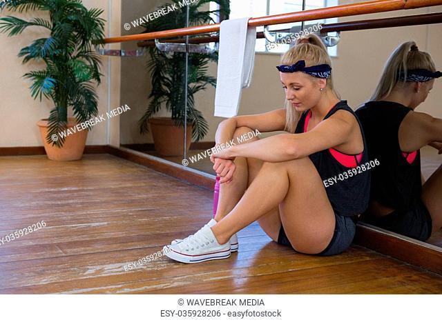 Full length of tired female dancer sitting at studio