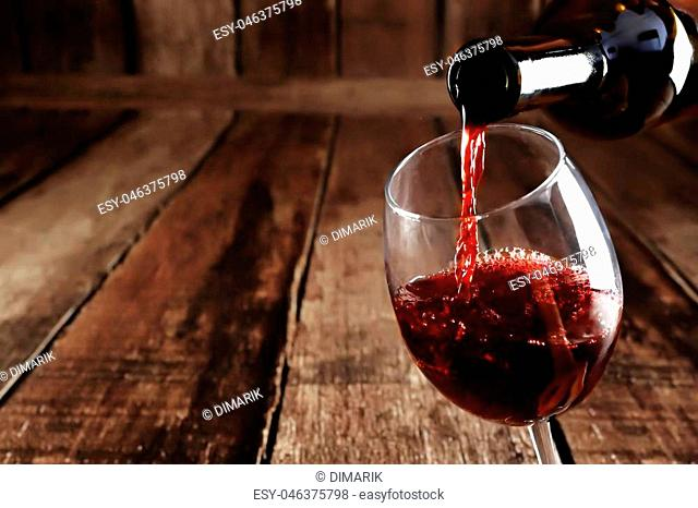 Red wine is poured from bottle to glass on wooden background