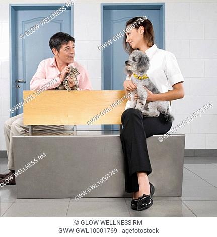 Man and a woman carrying their pets in a veterinary hospital