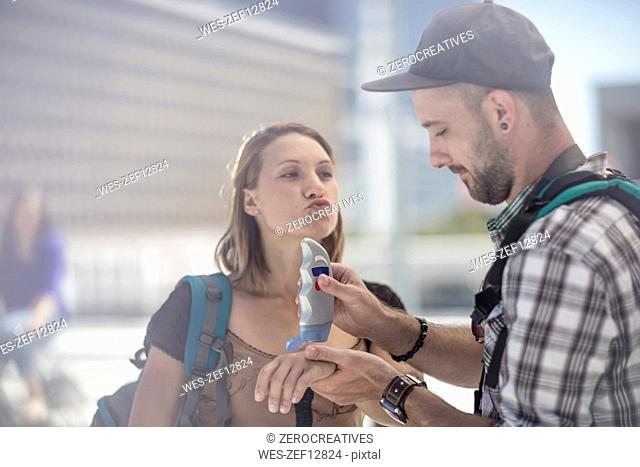 Young traveler couple applying sun cream