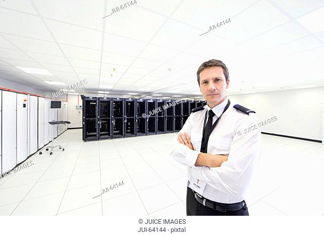 Security guard standing with arms crossed, looking at camera, in server room