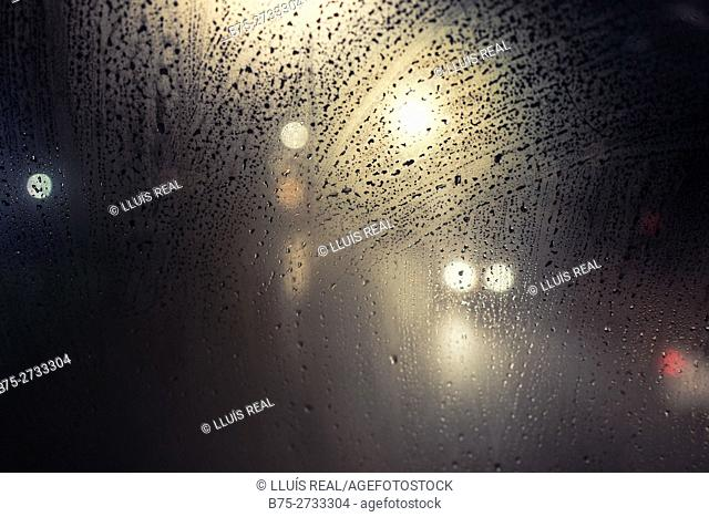 Bus window with water drops and light reflections on a rainy day. London, England