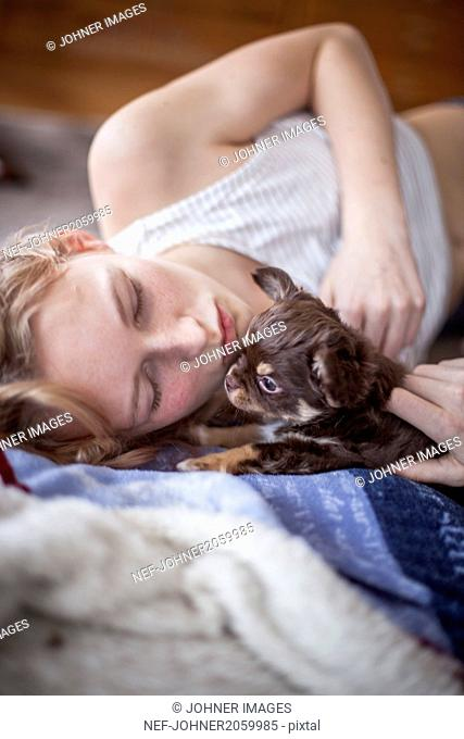 Girl with puppy lying down on bed