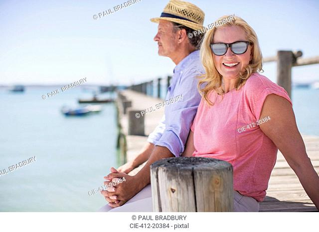 Couple holding hands together on wooden dock