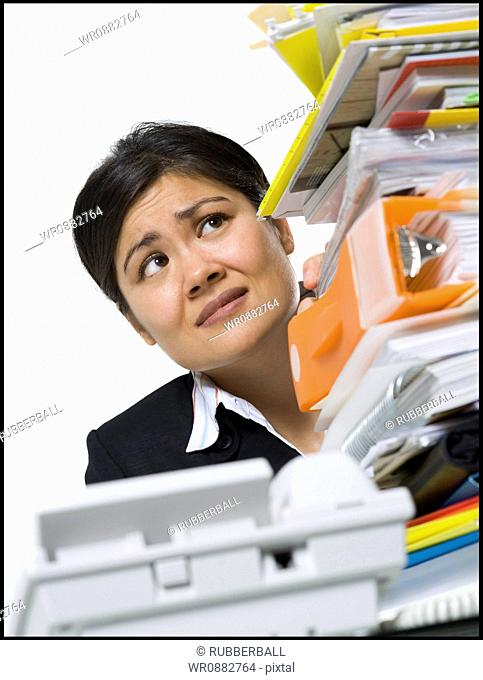 Low angle view of a businesswoman looking at a stack of files
