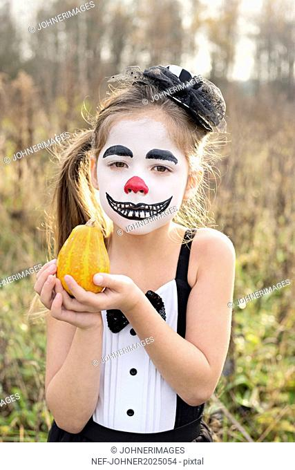 Portrait of girl with painted face holding pumpkin