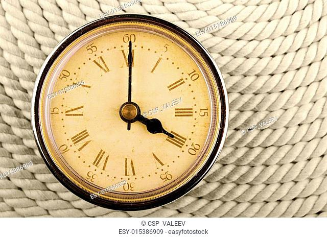 Clock with Roman numerals on cord background. 4