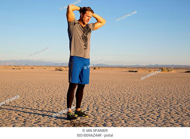 Man training, sweating with hands behind head on dry lake bed, El Mirage, California, USA