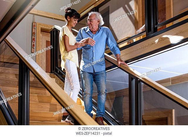 Nurse helping senior man to walk down the stairs