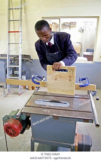 School boy using cut saw in woodwork classroom, St Mark's School, Mbabane, Hhohho, Kingdom of Swaziland