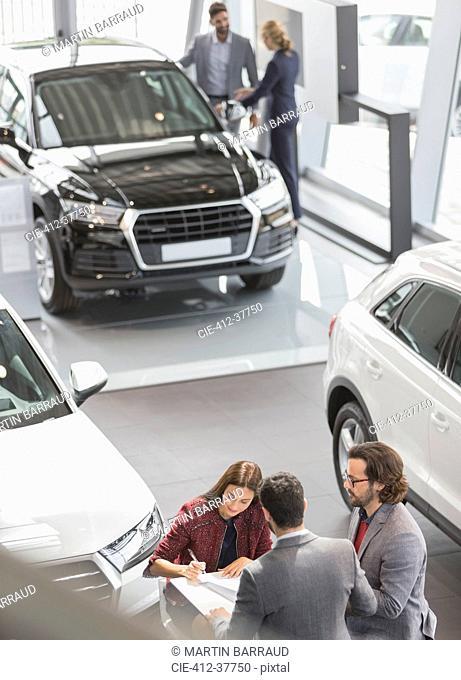 Car sales people and customers in car dealership showroom
