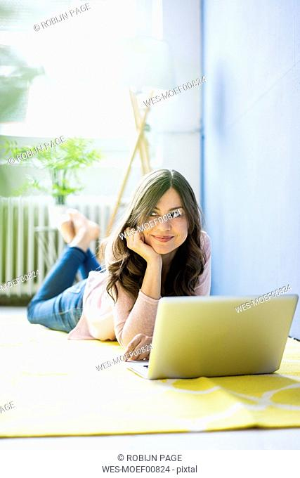 Smiling woman lying on floor with laptop