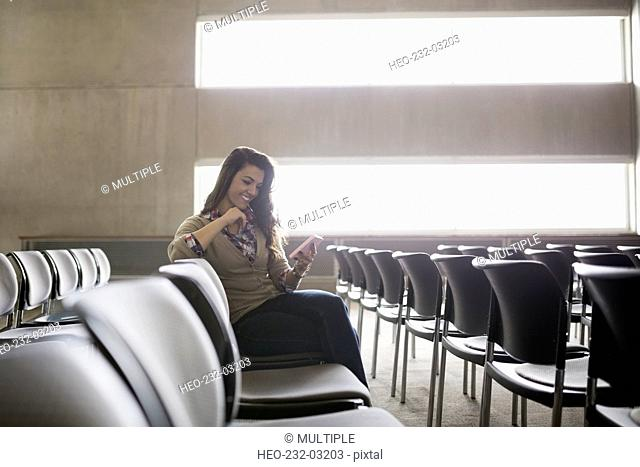Smiling student texting with cell phone auditorium seat
