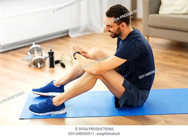 smiling man with fitness tracker exercising at home