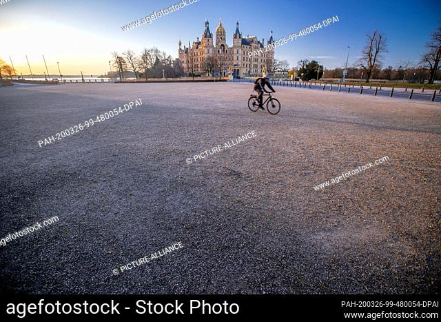 24 March 2020, Mecklenburg-Western Pomerania, Schwerin: A single cyclist is on the otherwise deserted Alte Garten in front of Schwerin Castle in the centre of...